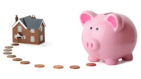 piggy bank following money to a house isolated on a white background